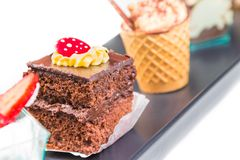 Delicious chocolate cake near little coffee and strawberry cakes Stock Photos