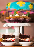Delicious chocolate cake pieces with cream filling sitting on small plates, pastry concept Royalty Free Stock Images