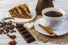 Delicious chocolate cake on a plate with a cup of coffee . Coffee beans, a piece of chocolate, anice, sugar and cinnamon sticks on Royalty Free Stock Photography