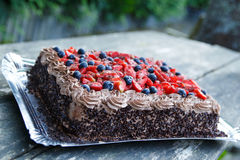 Delicious chocolate cake with strawberries and blueberries. Stock Photo