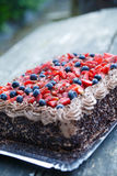 Delicious chocolate cake with strawberries and blueberries. Royalty Free Stock Photo