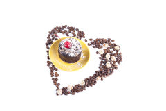 Delicious chocolate cake surrounded by heart shaped coffee beans Stock Photos