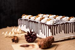 Delicious chocolate cake with whipped cream and walnut. On a festive table with Christmas decorations, fir cones, cinnamon sticks and a greeting card on black Stock Photo