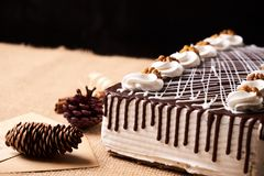 Delicious chocolate cake with whipped cream and walnut. On a festive table with Christmas decorations, fir cones, cinnamon sticks and a greeting card on black Stock Photography