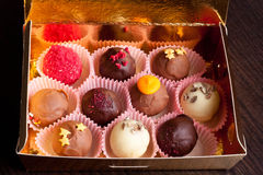 Delicious chocolate candies in gift box on table close-up. Delicious chocolate candies in gift box on table horizontal Stock Photography
