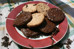 Delicious chocolate cookies on a plate with cloves Stock Image