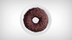 Delicious chocolate donut rotating on a white plate. Donut close-up. Top view.  stock video footage