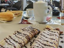 Delicious chocolate drizzled crepes with coffee and sandwich in stock photography