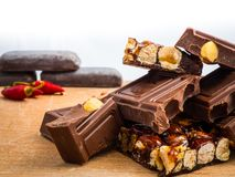 Delicious chocolate and Italian hazelnut nougat, cut into pieces, for a sea of sweetness. In the background other nougats and chillies. Taken up close, with stock image