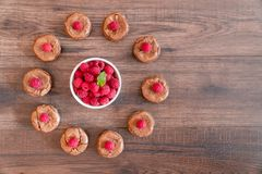 Delicious chocolate lava cakes with fresh raspberries and mint. Arranged in a circle on the wooden table with  white bowl of raspberries in the middle Royalty Free Stock Photos