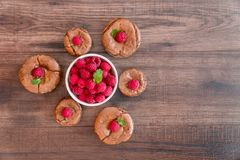 Delicious chocolate lava cakes with fresh raspberries and mint. Arranged in a triangle on the wooden table with  white bowl of raspberries in the middle Stock Photography