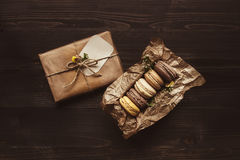 Delicious chocolate macaroons and gift on the wooden table, top view Stock Photography