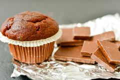 Muffin. Delicious chocolate muffin on chocolate bar with cocoa powder on black background. Muffin background Stock Photo