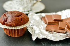 Muffin. Delicious chocolate muffin on chocolate bar with cocoa powder on black background. Muffin background Royalty Free Stock Images
