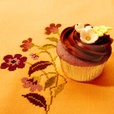 Delicious chocolate muffin on vintage tablecloth Stock Photos