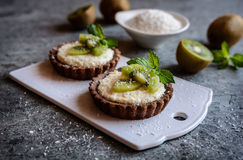 Chocolate tartlets filled with coconut cream and topped with kiwi slices. Delicious chocolate tartlets filled with coconut cream and topped with kiwi slices Royalty Free Stock Image