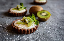 Chocolate tartlets filled with coconut cream and topped with kiwi slices. Delicious chocolate tartlets filled with coconut cream and topped with kiwi slices Stock Image
