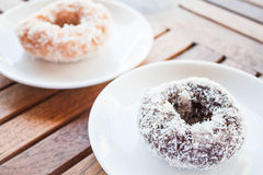 Delicious chocolate and vanilla coconut donuts on wooden table Stock Photos