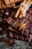 Delicious chocolates and spices on a dark background. Royalty Free Stock Images