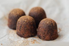 Delicious chocolates truffles with cocoa on paper Stock Images