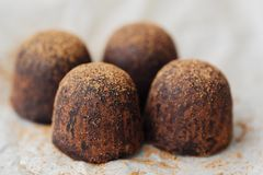 Delicious chocolates truffles with cocoa on paper Stock Photography