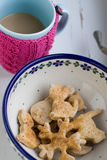 Delicious Christmas cookies on the plate and a cup of coffee with milk in a knitted pink sweater Stock Images