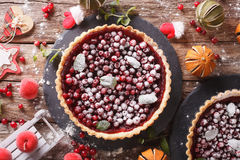 Delicious Christmas cranberry tart and festive decoration close-. Up on the table. horizontal view from above Stock Image