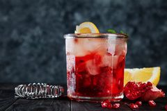 Delicious close up view on red alcoholic cocktail. Glass with ice, beverage, lemon and bar utensils on dark wooden background. stock photos