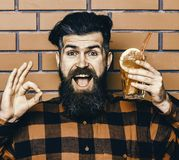 Delicious cocktails concept. Hipster enjoy drink or cocktail. Man shows ok gesture on brick wall background. Hipster with beard and happy face holds glass with Royalty Free Stock Images