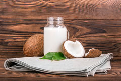 Delicious coconut milk, organic coconuts with fresh green leves on a dark wooden background. Coconuts with fresh green leaves and a mason jar of coconut milk on Royalty Free Stock Photography
