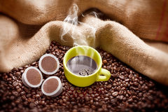 Delicious coffee. Steaming coffee cup with roasted beans, coffee capsule (for modern machines) and hessian sack Stock Images