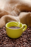 Delicious coffee. Steaming coffee cup with roasted beans and hessian sack Royalty Free Stock Photos