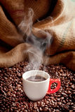 Delicious coffee. Steaming coffee cup with roasted beans and hessian sack Royalty Free Stock Photography