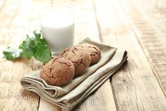 Delicious coffee cookies on napkin and glass of milk. On wooden table Royalty Free Stock Images