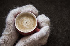 Delicious coffee warms the cold winter. Delicious warming coffee in the red circle in the winter cold in the hands of girl in knitted gloves Stock Photos