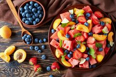Fresh fruit salad on a plate. Delicious colorful fresh fruit salad with watermelon, blueberries, peach slices, strawberry and lime on a clay plate on an old Stock Photo