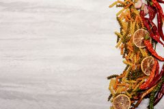 Delicious colorful italian pasta and ingredients on textured background. Delicious colorful Italian pasta , chili pepper, orange, garlic, star anise on grey stock image