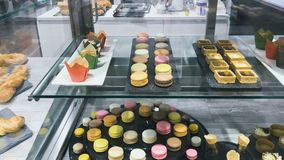 Delicious colorful sweets. At the shelf in the shop. Cupcakes, macaroons, desserts, puff pastries at the transparent shelves. The counter behind the cupboard stock footage