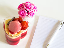 Delicious Colorful yogurt cake with pen on notebook and pink roses on white table. Colorful yogurt cake with pen on notebook and pink roses on white table Stock Photography