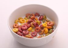 Delicious coloured Cereal with Milk. In bowl on white background Stock Photography