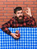 Delicious concept. Barman with beard on cheerful face holds cocktail and shows ok gesture. Bartender recommends to try. Beverage. Man in checkered shirt near Royalty Free Stock Images