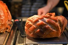 Delicious cooked and resting whole joint of roast gammon with turkey in the background. A delicious whole roasted pork ham or gammon joint of meat cooked and Royalty Free Stock Photography