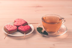Delicious cookies in the shape of a heart on a white plate on wooden background. Cup of green tea. Breakfast Stock Photos