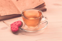 Delicious cookies in the shape of a heart on a white plate on wooden background. A Cup of green tea.Breakfast Stock Photos