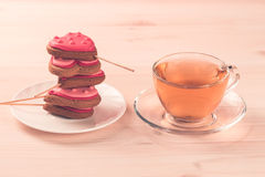 Delicious cookies in the shape of a heart on a white plate on wooden background. Cup of green tea. Breakfast Royalty Free Stock Photography
