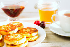 Delicious cottage cheese pancakes with cherry jam and honey. Royalty Free Stock Photo