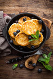Delicious cottage cheese pancakes or syrniki with fresh blueberry in cast-iron pan on dark wooden rustic background, above view. T Royalty Free Stock Photos