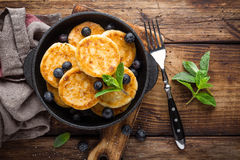 Delicious cottage cheese pancakes or syrniki with fresh blueberry in cast-iron pan on dark wooden rustic background, above view. T Royalty Free Stock Photography