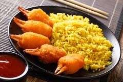 Delicious crab claws in deep fried with a garnish of yellow rice. And tomato sauce close-up on a plate on the table. horizontal stock photography