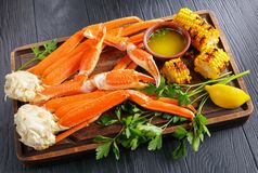 Snow Crab legs served with corn cobs. Delicious Crab legs served with melted butter in clay bowls, garlic cloves, lemon slices, grilled corn in cobs and fresh royalty free stock photos